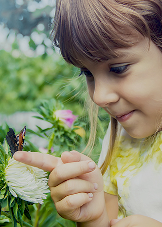 Smiling girl playing with a butterfly at a park.