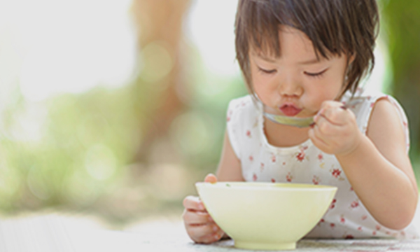 Toddler blowing on hot soup.