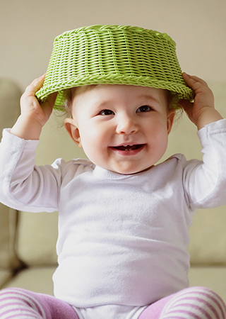 Smiling baby holding green woven basket over head.