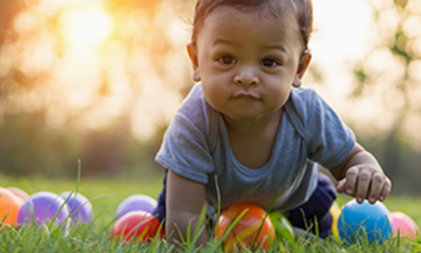 Baby playing with balls and crawling at a park.