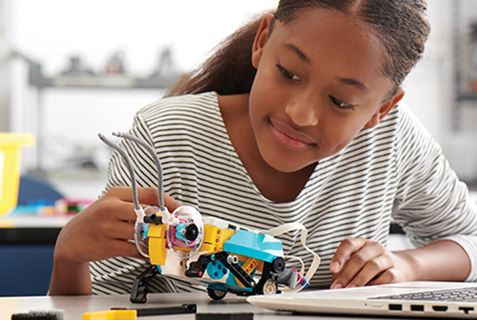 Female student building a Lego Spike insect robot.