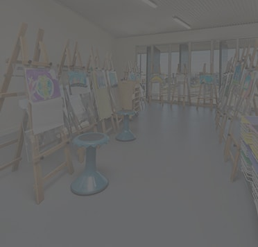 Greyed out image of art classroom with easels, canvases, stools and art supplies.
