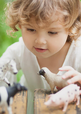 Engaged kid playing with farm animal figurines at a park.