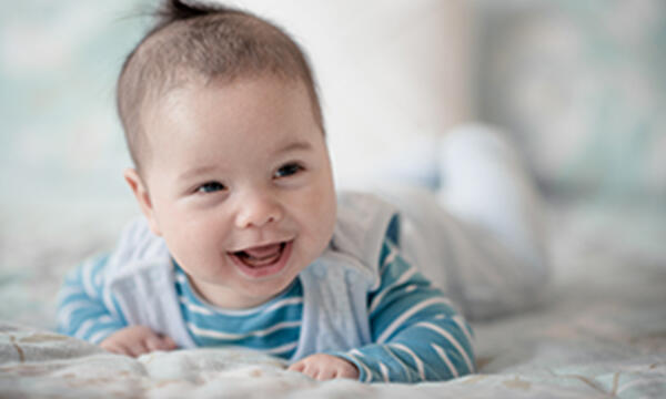 Smiling baby crawling on bed.