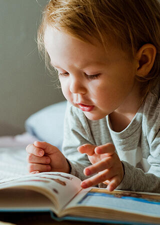 Toddler reading a book in bed.