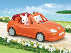 Two Sylvanians driving by the ocean side in an orange convertible car